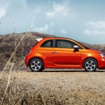 side view of electric orange Fiat 500e on the beac
